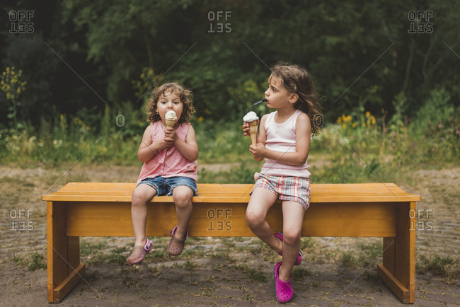 Little girls sitting on a bench eating ice cream cones