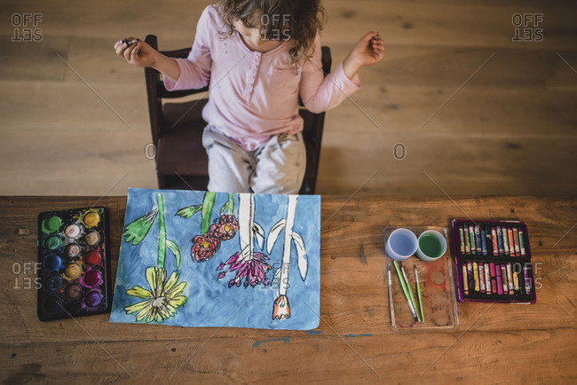 Little girl painting flowers at the table