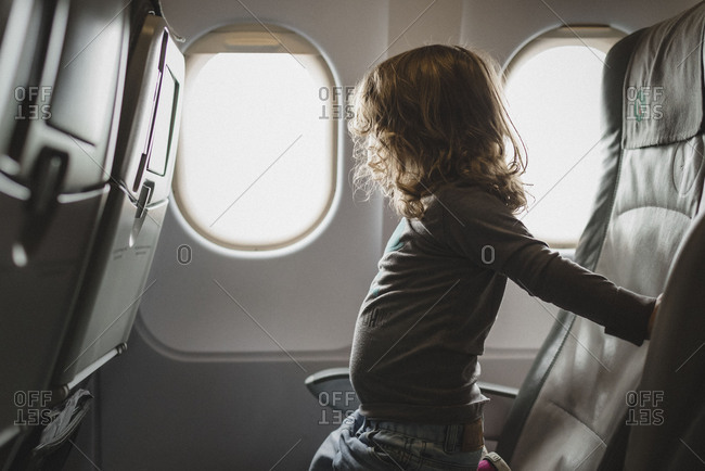 Little girl looking out the window of an airplane