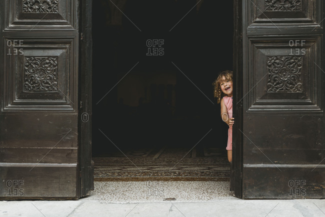 Little girl laughing while looking out the door of an old building