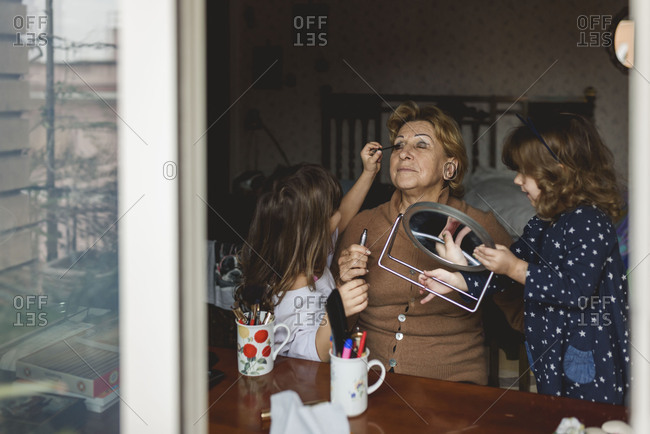Two little girls helping their grandmother put makeup on