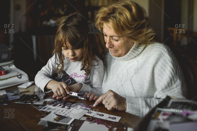 Young girl looking at old photos with her grandmother