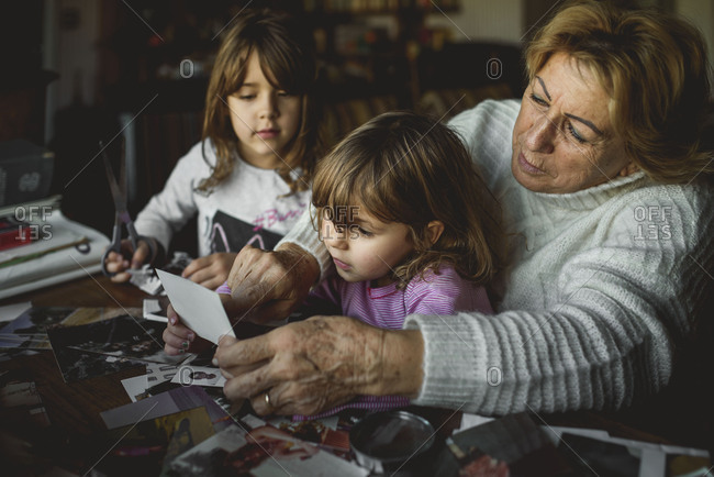 Young girls looking at old photos with their grandmother