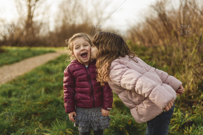 Young girl giving her little sister a kiss