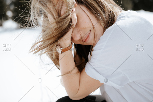 Woman wearing white shirt tousling her hair