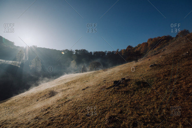 Sunrise over hillside with mist in Romania