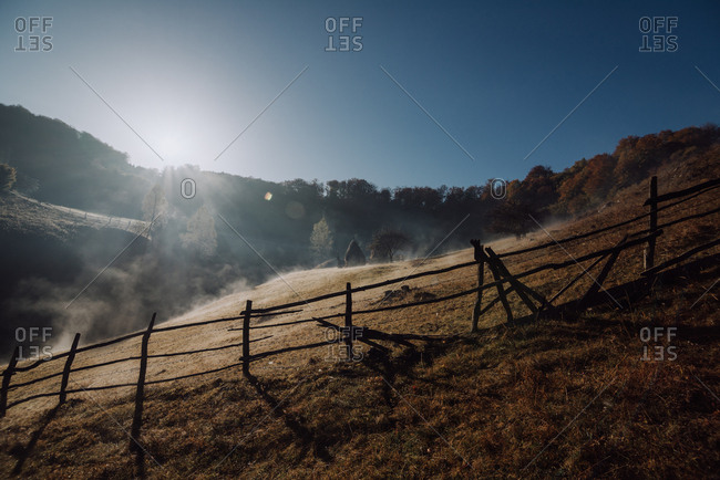 Sunrise over hillside with fence in Romania