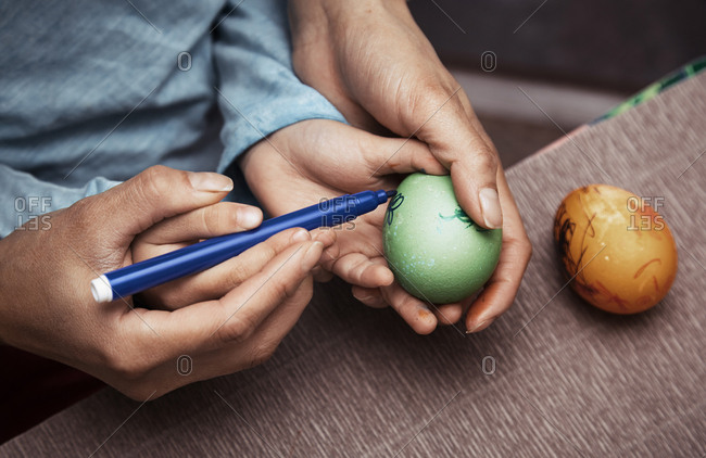 Mother assisting child to draw on Easter eggs