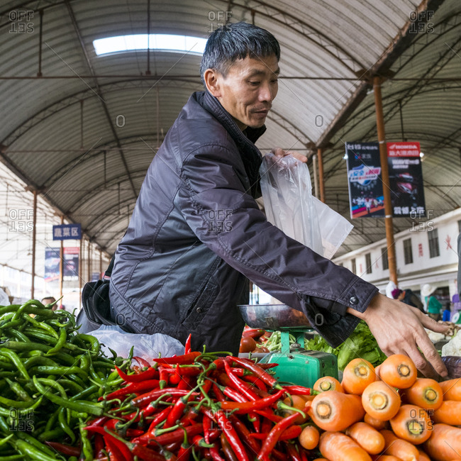 Menglian, Yunnan, China - 2/27/16: Man bagging vegetables in a Chinese market