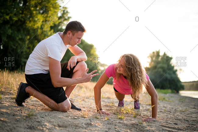 Young and fit woman training outside with coach in summer