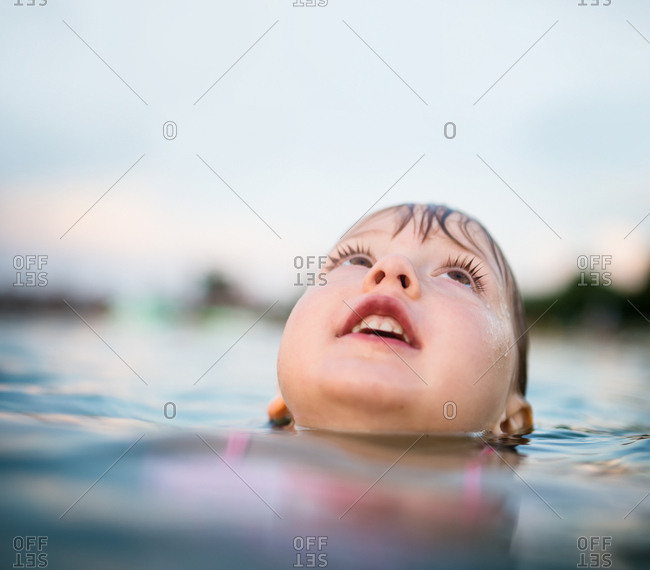 Little girl swimming in lake looking up