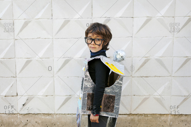 Side view of young boy in glasses wearing cardboard robot costume