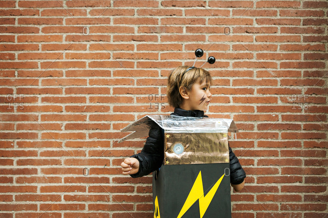 Boy in robot costume standing by brick wall