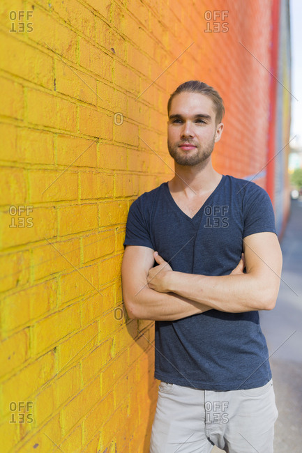 Man leaning against a brightly colored wall