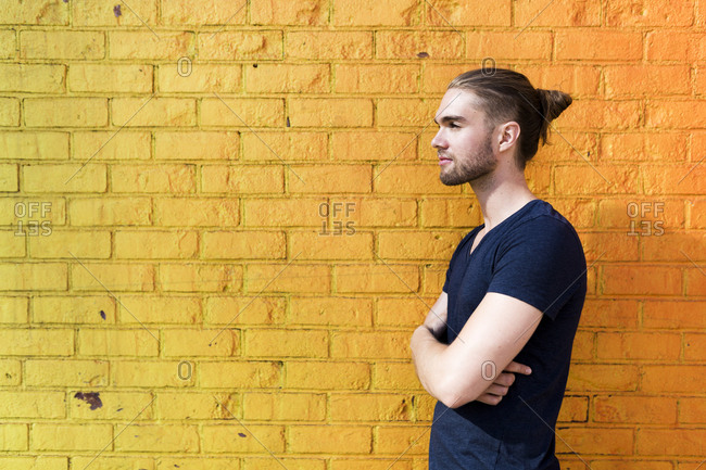 Profile view of a man against a bright yellow and orange wall