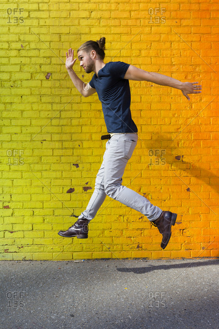 Young man jumping in front of colorful wall