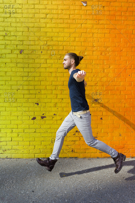 Young man skipping in front of colorful wall