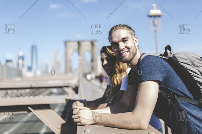 Two young people looking out across the Brooklyn bridge overpass