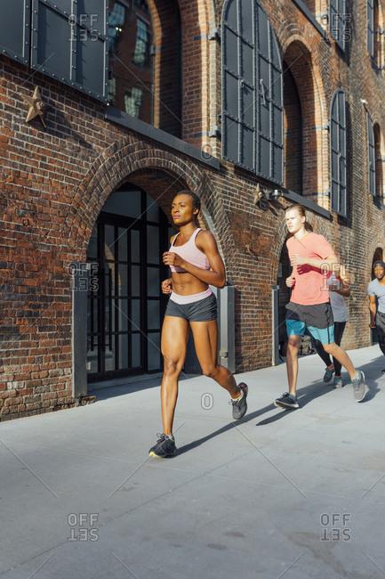 Happy friends running in Brooklyn, New York City