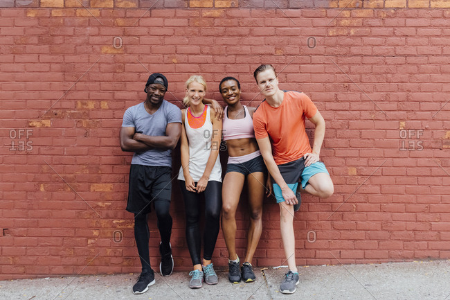 Portrait of a group of friends smiling and hanging out against a brick wall