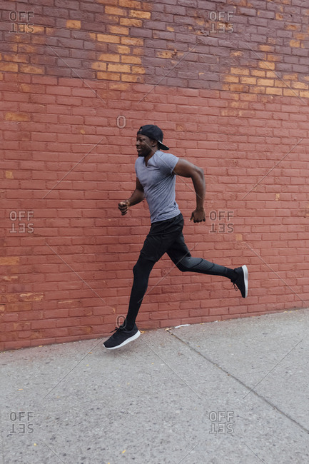 Black young man running on the street in Brooklyn, New York