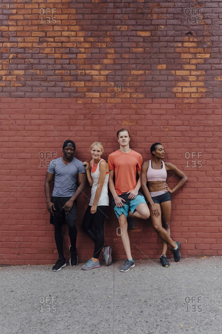 Portrait of a group of friends against a brick wall after working out
