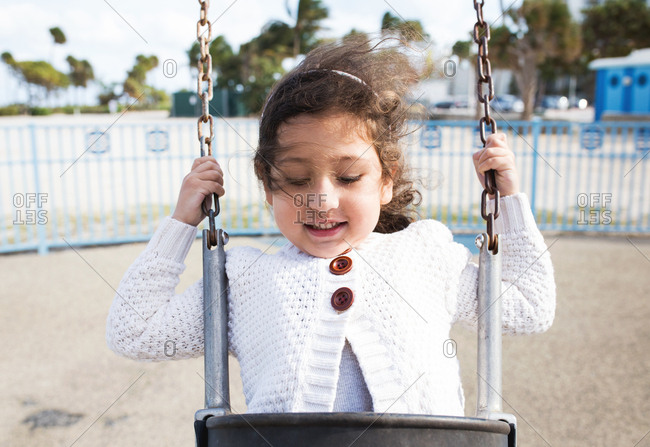 Close-up of a young girl swinging on a beachside playground