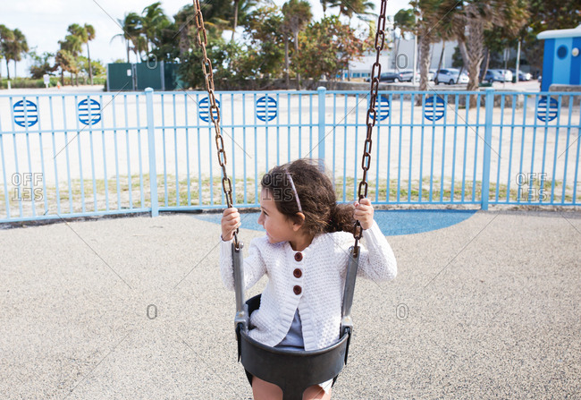 Young girl swinging in a beachside playground