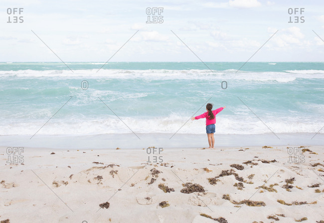 Girl greeting the ocean with open arms