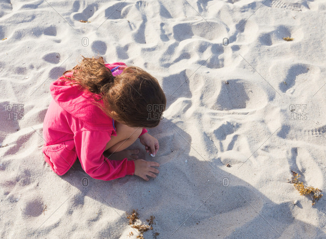 Young girl playing with shells on the beach