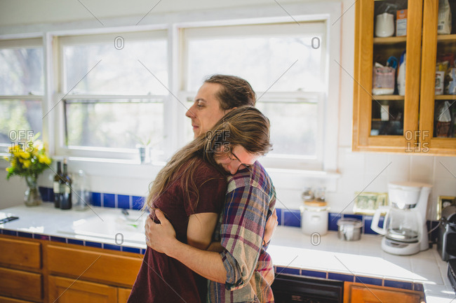 Cute couple hugging in kitchen with beautiful back light