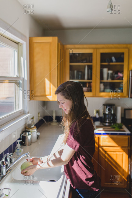 Young woman washing cilantro in sink