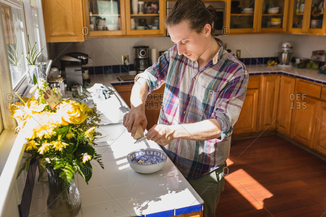 Man grating cheese into a bowl