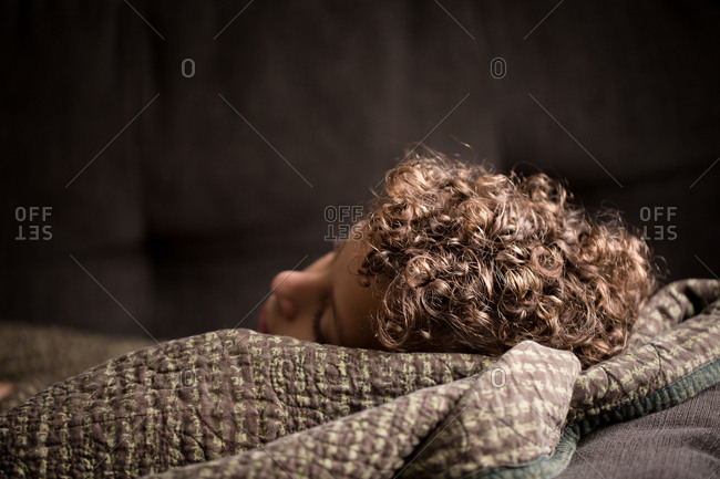 Curly hair of young boy resting on quilt