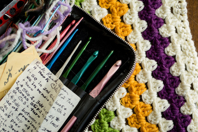 Handwritten crochet pattern in case with crochet hooks on afghan