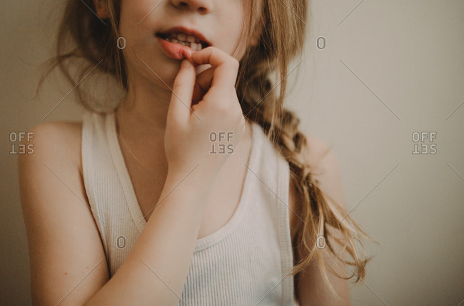 Young girl touching her lower lip