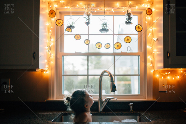 Girl looking at string of Christmas lights decorating kitchen window