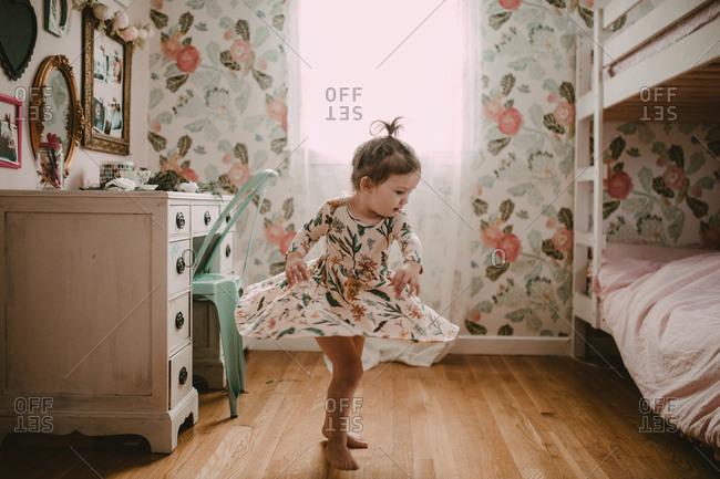 Girl twirling flowered dress in bedroom