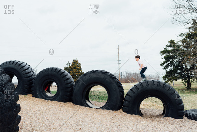 Young boy playing on truck tires