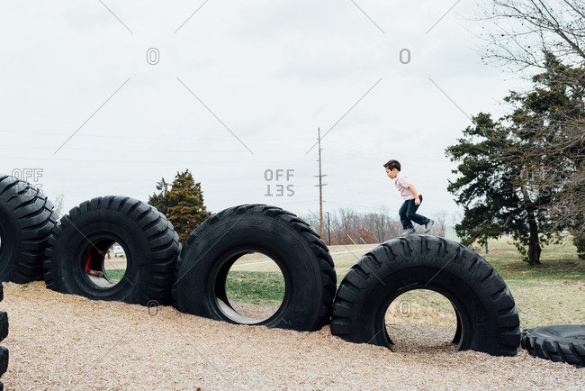 Young boy climbing on giant truck tires