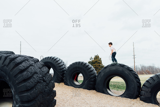 Row of giant truck tires on playground with boy