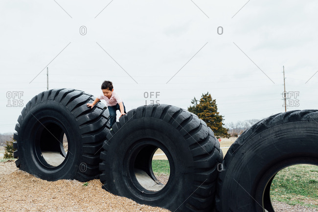 Child climbing on giant truck tires