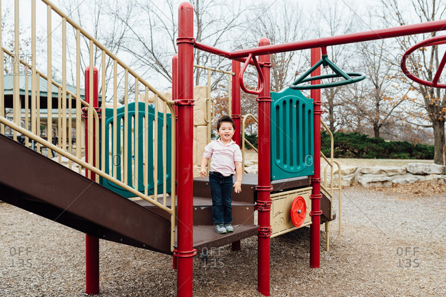 Little boy playing at playground climbing structure