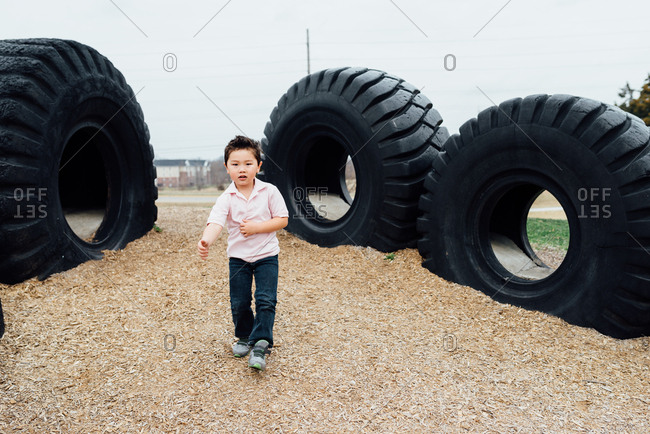 Young boy standing on playground with truck tires