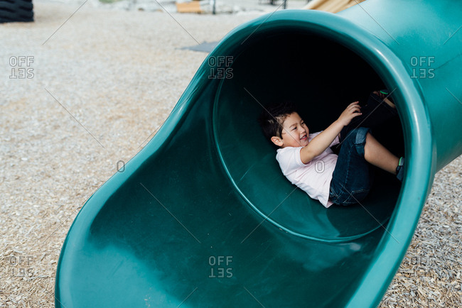 Young boy playing in a tunnel slide