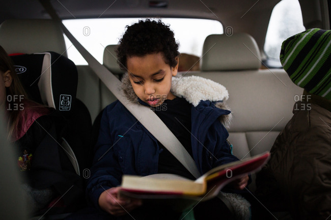 Girl reading book riding in car