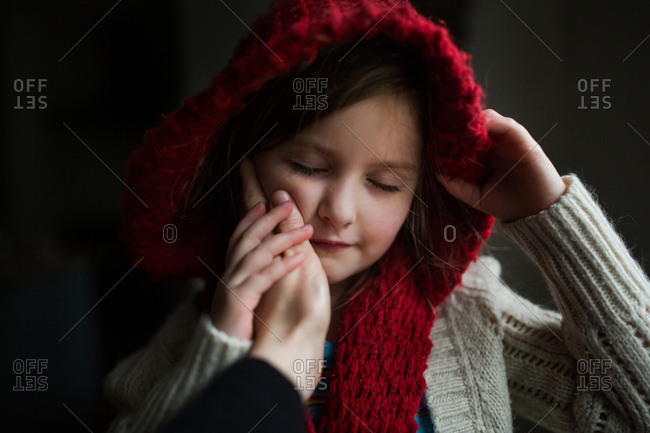 Hand caressing cheek of girl in scarf