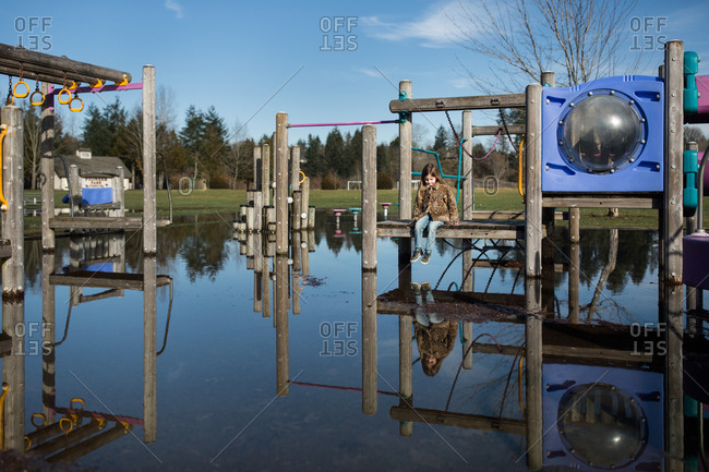 Girl on playground structure over water