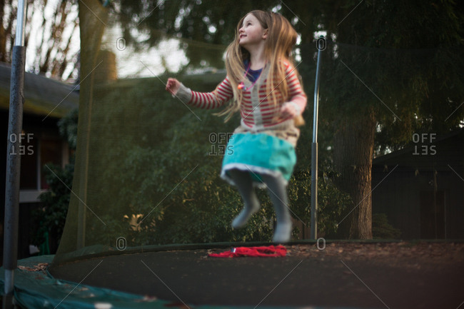 Girl in midair bounce on trampoline