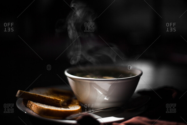 A steaming bowl of soup and toast
